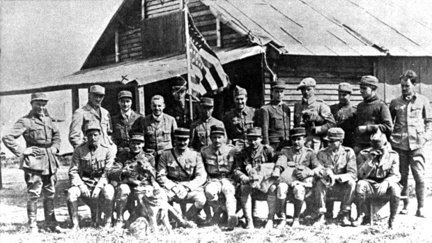 "The Escadrille Lafayette in July 1917. Standing, left to right are Soubiron, Doolittle, Campbell, Persons, Bridgman, Dugan, MacMonagle, Lowell, Willis, Jones, Peterson and de Maison-Rouge (French Deputy Commander). Seated, left to right are Hill, Masson with ""Soda,"" Thaw, Thenault (the French Commander), Lufbery with ""Whiskey,"" Johnson, Bigelow and Rockwell. (U.S. Air Force photo)"
