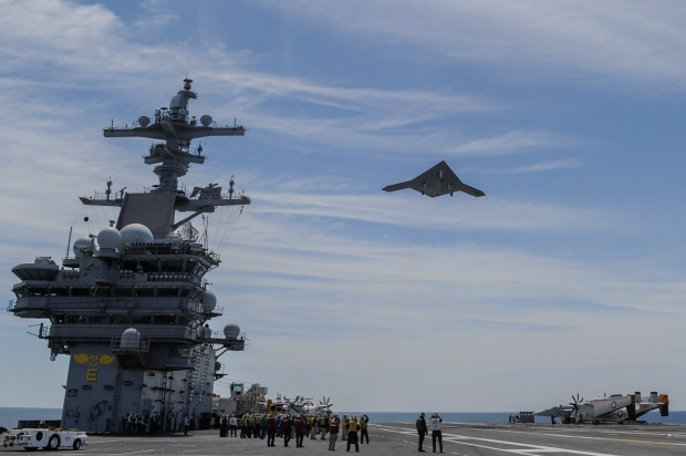 An X-47B Unmanned Combat Air System (UCAS) demonstrator flies over the aircraft carrier USS George H.W. Bush (CVN 77) May 14. George H.W. Bush is the first aircraft carrier to successfully catapult launch an unmanned aircraft from its flight deck. (U.S. Navy photo courtesy of Northrop Grumman by Alan Radecki/Released)