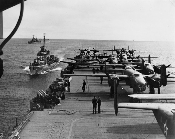 On 18 April 1942, airmen of the US Army Air Forces, led by Lt. Col. James H. (Jimmy) Doolittle, carried the Battle of the Pacific to the heart of the Japanese empire with a surprising and daring raid on military targets at Tokyo, Yokohama, Yokosuka, Nagoya, and Kobe. This heroic attack against these major cities was the result of coordination between the Army Air Forces and the US Navy, which carried the sixteen North American B-25 medium bombers aboard the carrier USS Hornet to within take-off distance of the Japanese Islands. Here, a pair of alert escorts follow the USS Hornet to protect her lethal cargo of B-25 bombers. (U.S. Air Force Photo)