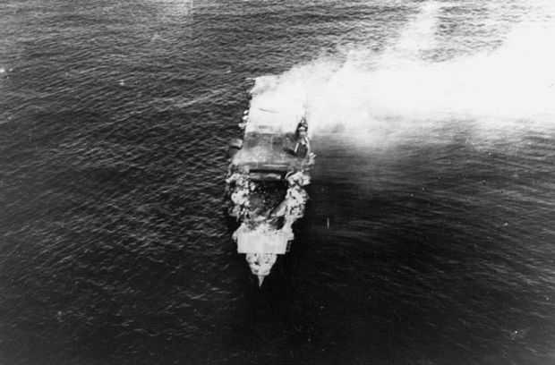 The burning Japanese aircraft carrier Hiryu, photographed by a plane from the carrier Hosho shortly after sunrise on 5 June 1942. Hiryu sank a few hours later. Note collapsed flight deck over the forward hangar.