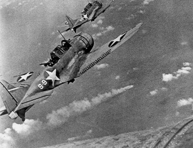 "U.S. Navy Douglas SBD-3 ""Dauntless"" dive bombers from scouting squadron VS-8 from the aircraft carrier USS Hornet (CV-8) approaching the burning Japanese heavy cruiser Mikuma to make the third set of attacks on her, during the Battle of Midway, 6 June 1942. Mikuma had been hit earlier by strikes from Hornet and USS Enterprise (CV-6), leaving her dead in the water and fatally damaged. Note bombs hung beneath the SBDs. (US Navy Photograph)"