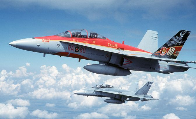 "Two Canadian Forces 410 Squadron CF-188B Hornet fighter flying over the Utah Test and Training Range (USA) for planned engagements during the ""Tiger Meet of the Americas"" on 9 August 2001. The first aircraft is painted in a special scheme commemorating the 60th anniversary of 410 Squadron. USAF Photograph by SSgt Greg L. Davis."