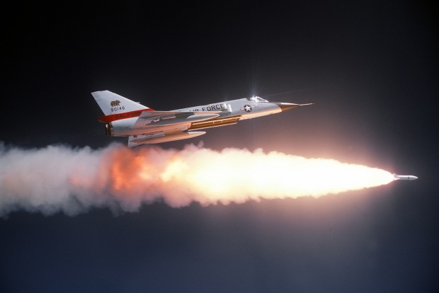 An air-to-air right side view of an F-106 Delta Dart aircraft after firing an ATR-2A missile over a range.  An auxiliary fuel tank is on each wing.  The aircraft is assigned to the 194th Fighter Interceptor Squadron, California Air National Guard. (U.S. Air Force Photograph/Released)