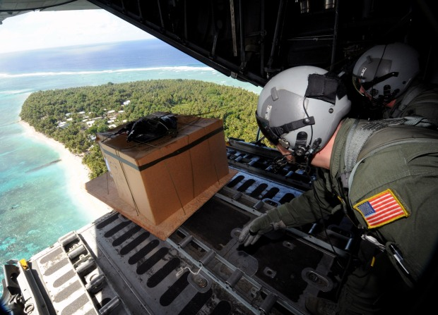 Operation Christmas Drop 2008: Tech. Sgt. Heath Bahyi and Chief Master Sgt. Michael Sundberg push out a boxed pallet of donated goods from a C-130 Hercules during Operation Christmas Drop Dec. 19 over the remote Island of Yap. Airmen today continue the tradition of delivering supplies to remote islands of the Commonwealth of the Northern Marianas Islands, Yap, Palau, Chuuk and Pohnpei. In all, more than 180 boxes were built for the humanitarian mission, making 2008 one of the largest drops in Operation Christmas Drop's 57-year history. Sergeant Bahyi and Chief Sundberg are loadmasters from the 36th Airlift Squadron from Yokota Air Base, Japan. (U.S. Air Force photograph/Released)