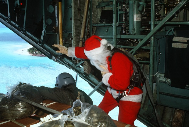 Dec. 14, 1990. Santa Claus (Capt. Mike d'Albertis, 605th Military Airlift Support Squadron) and Staff Sgt. Tony Thompson, loadmaster with the 21st Tactical Airlift Squadron, watch as a Christmas Drop container is parachuted toward its destination. The annual airdrop is a humanitarian effort providing aid to needy islanders throughout Micronesia during the Christmas season. (U.S Air Force Photograph by Tech. Sgt. James Ferguson/Released)