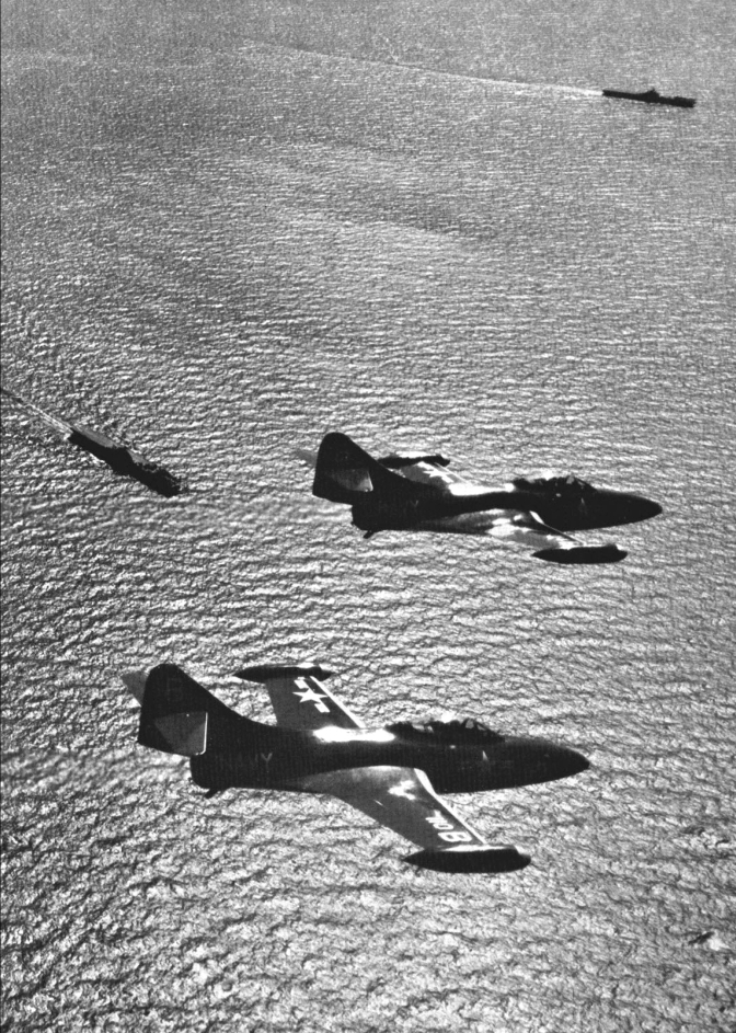 "Two U.S. Navy Grumman F9F-2 Panthers of Fighter Squadron VF-191 ""Satan's Kittens"" return to the aircraft carrier USS Princeton (CV-37), visible in the foreground below. VF-191 was assigned to Carrier Air Group 19 (CVG-19) for a deployment aboard the Princeton from 9 November 1950 to 29 May 1951. In the background is USS PHilippine Sea (CV-47), which was deployed to Korea from 5 July 1950 to 9 June 1951 with CVG-11 and CVG-2. (Official Naval Historical Center photo)"