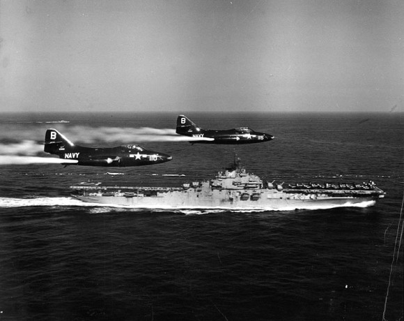 Two U.S. Navy Grumman F9F-2 Panther fighters of fighter squadron VF-191 Satan's Kittens, assigned to Carrier Air Group 19 (CVG-19), fly past their parent aircraft carrier USS Princeton (CV-37) in 1951 dumping fuel prior to landing. The carrier was deployed to Korea from 9 November 1950 to 29 May 1951. (Official Naval Historical Center photo)