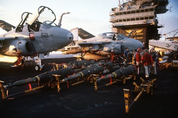 Laser-guided bombs line the flight deck of the aircraft carrier USS JOHN F. KENNEDY (CV-67) in preparation for air strikes against Iraq during  Operation Desert Storm.  The A-6E Intruder aircraft in the background is armed with laser-guided bombs.
